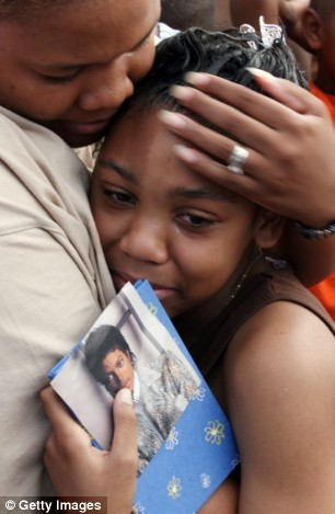 Tears for a hero: Fans, with tears streaming down their faces, comfort each other outside Michael Jackson's home in Los Angeles, where the singer collapsed earlier today