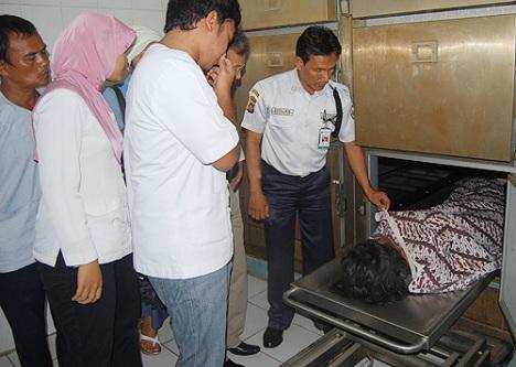 Petugas keamanan memperlihatkan jasad Anggi kepada anggota keluarga di kamar jenazah RSUP dr M Djamil, Selasa (16/6).