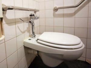 The woman slipped and became stuck with one foot either side of the toilet, and her back against the door
